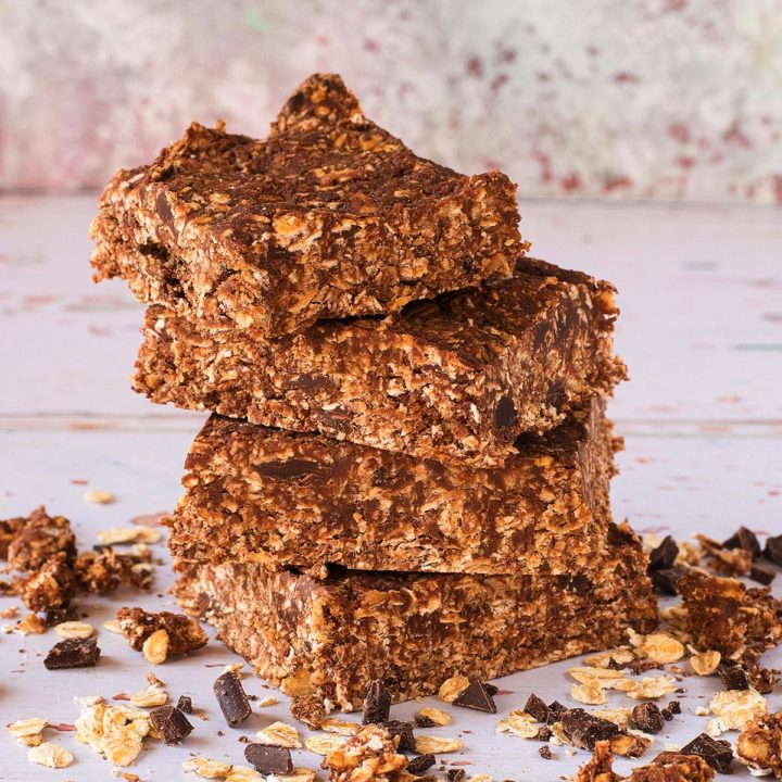 A stack of four Chocolate Peanut Butter Oat Squares surrounded by crumbs on a wooden surface