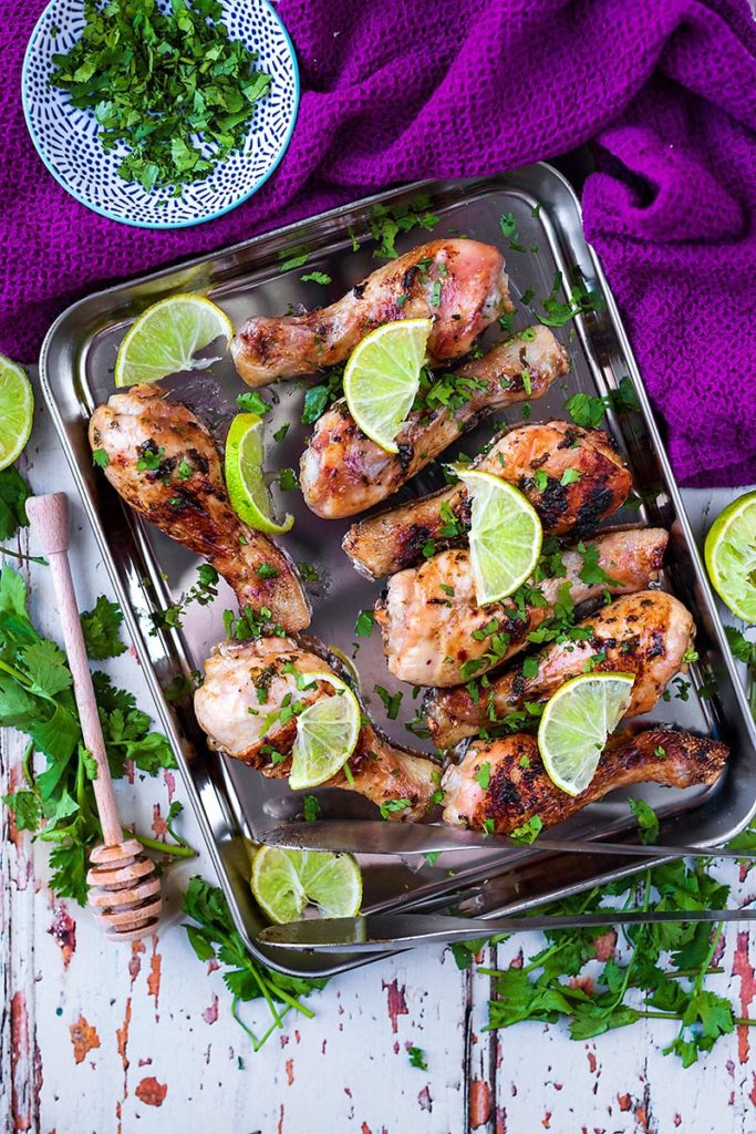 Eight cooked honey lime chicken drumsticks on a baking sheet