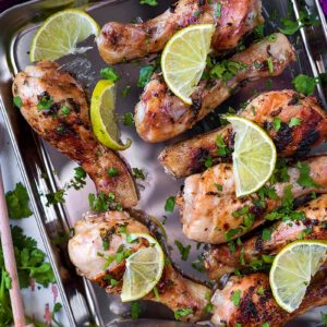Honey Lime Chicken on a baking sheet topped with herbs and lime slices
