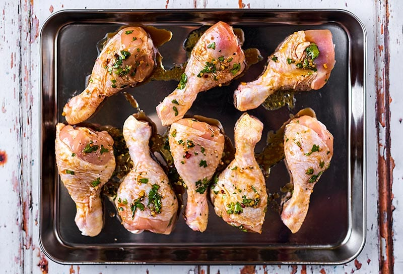 Eight marinated chicken drumsticks on a baking tray