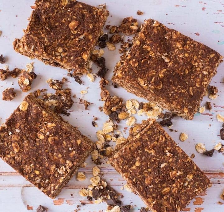 Four No-Bake Chocolate Peanut Butter Oat Squares surrounded by crumbs on a wooden surface