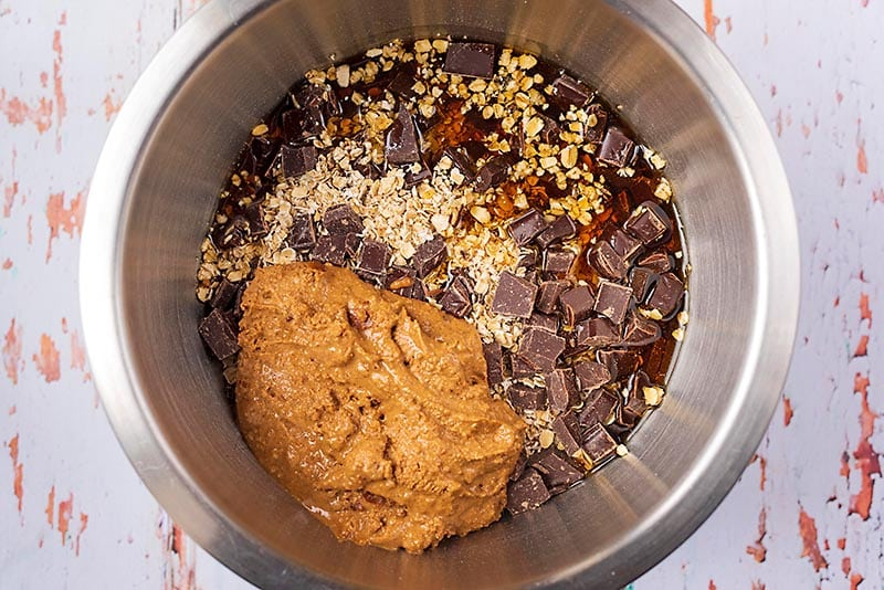 A mixing bowl containing oats, chocolate chunks, maple syrup and melted nut butter