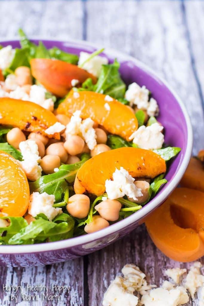 Apricot, Chickpea and Feta Salad in a purple bowl with half apricots next to it