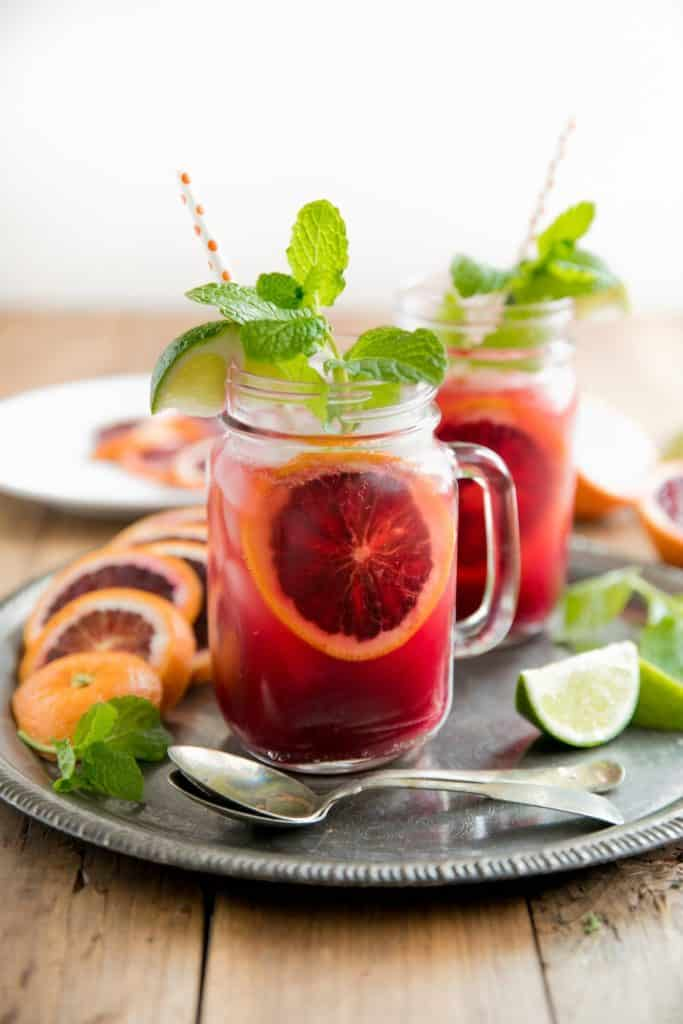 A deep red coloured drink in a mason jar with mint leaves sticking out