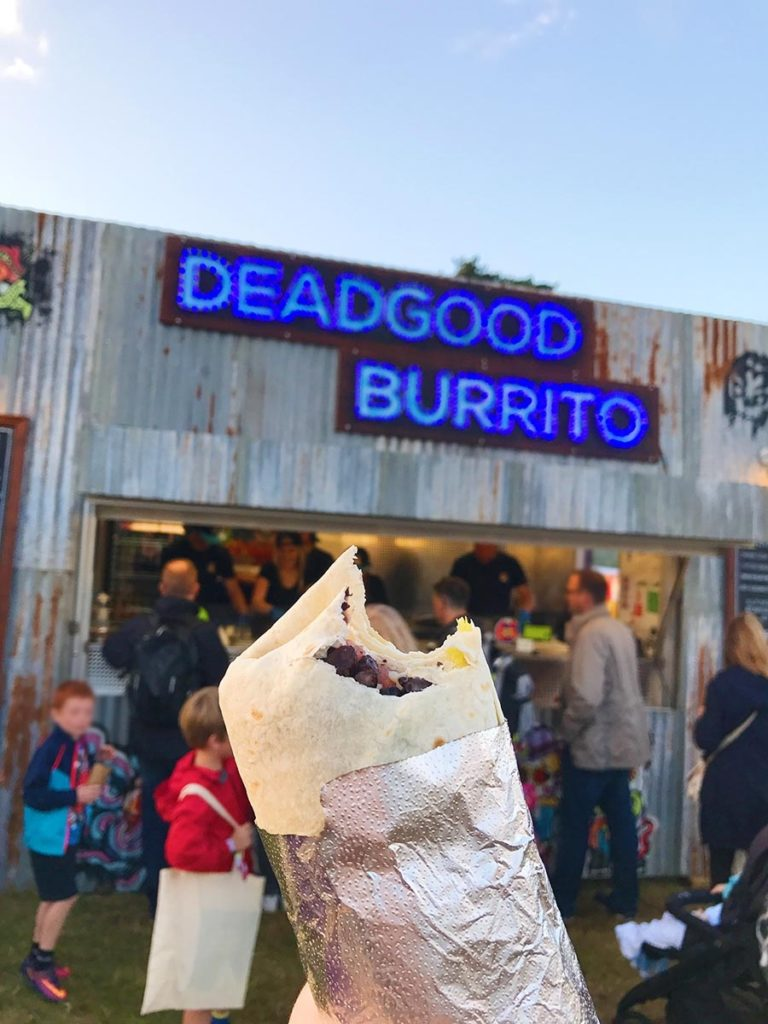 A burrito being held up in front of a burrito stall called Dead Good Burrito