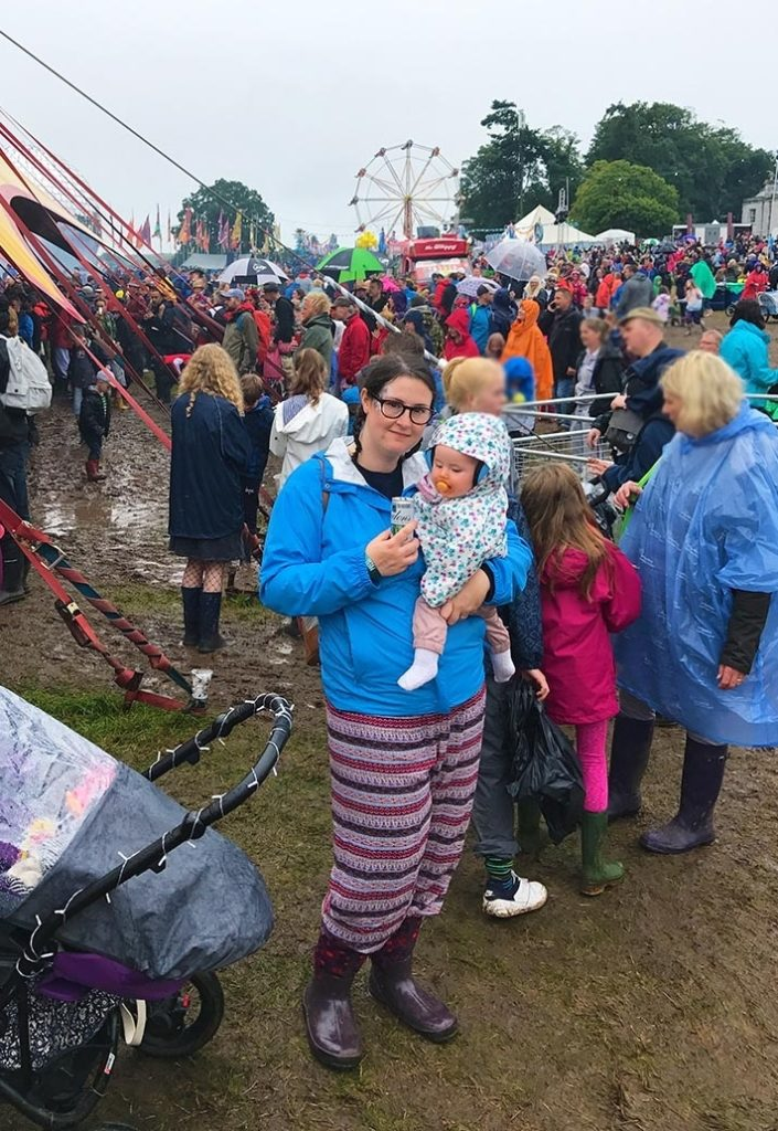 A woman holding a baby at a muddy festival