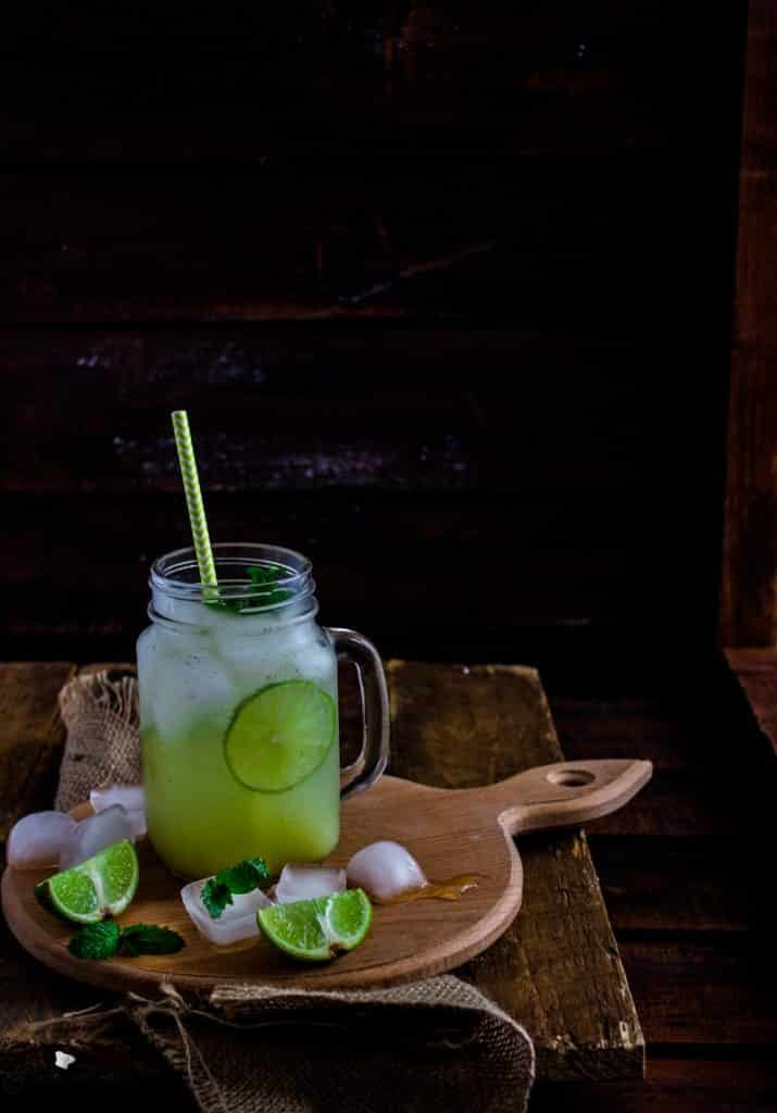 A green iced drink in a mason jar sat on a wooden serving board