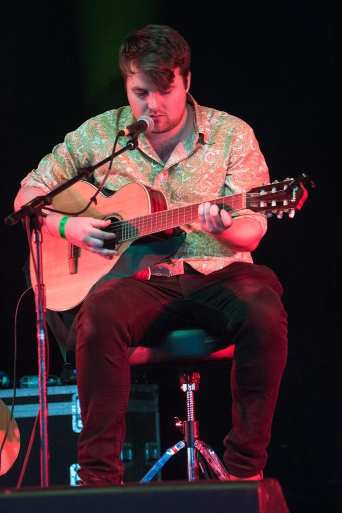 The singer songwriter Swan Levitt sat on a stool playing guitar