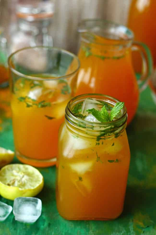 A dark orange drink in a jar with ice and mint leaves