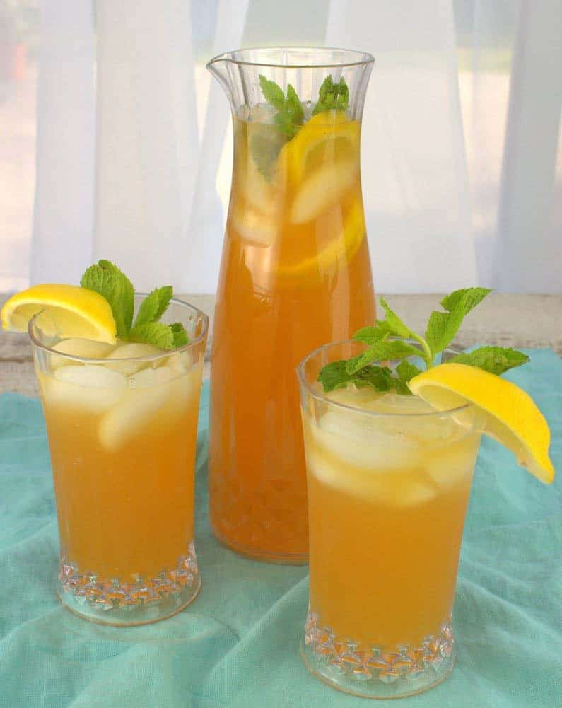 Two glasses of yellow iced tea in front of a jug of more iced tea