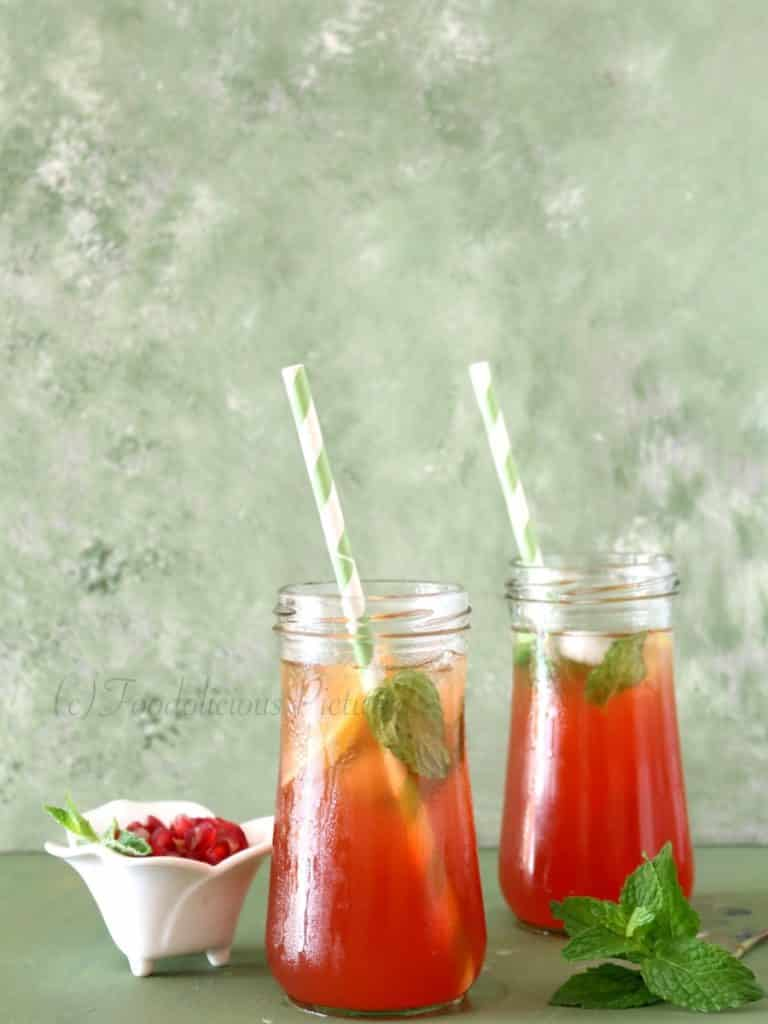 Two tall jars containing a red coloured drink with slices of lemon and mint leaves