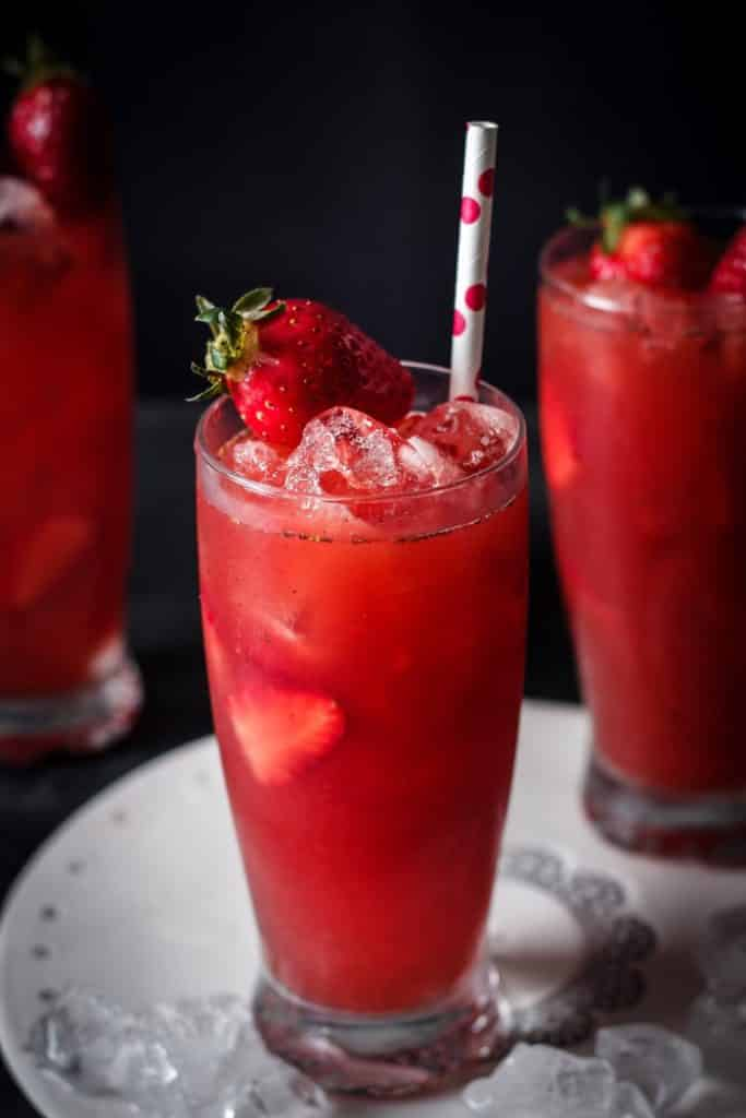 A res strawberry drink in a tall glass with ice and a straw