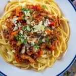 A white plate with mushroom bolognese and spaghetti