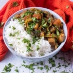Aubergine Masala in a blue bowl next to an orange towel