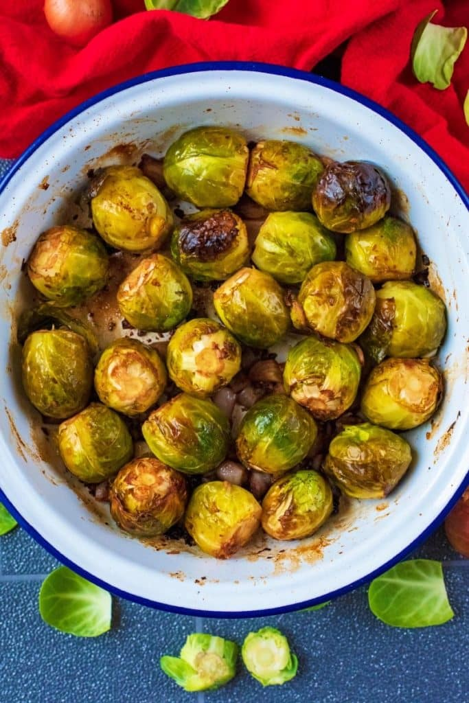 A white dish with Balsmaic Roasted Brussels Sprouts. A red towel is next to it