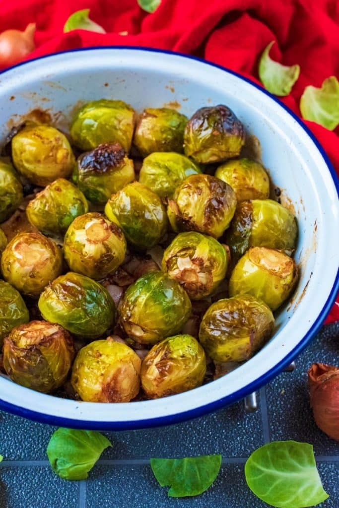 Brussel sprouts in a white dish with sprout leaves scattered around