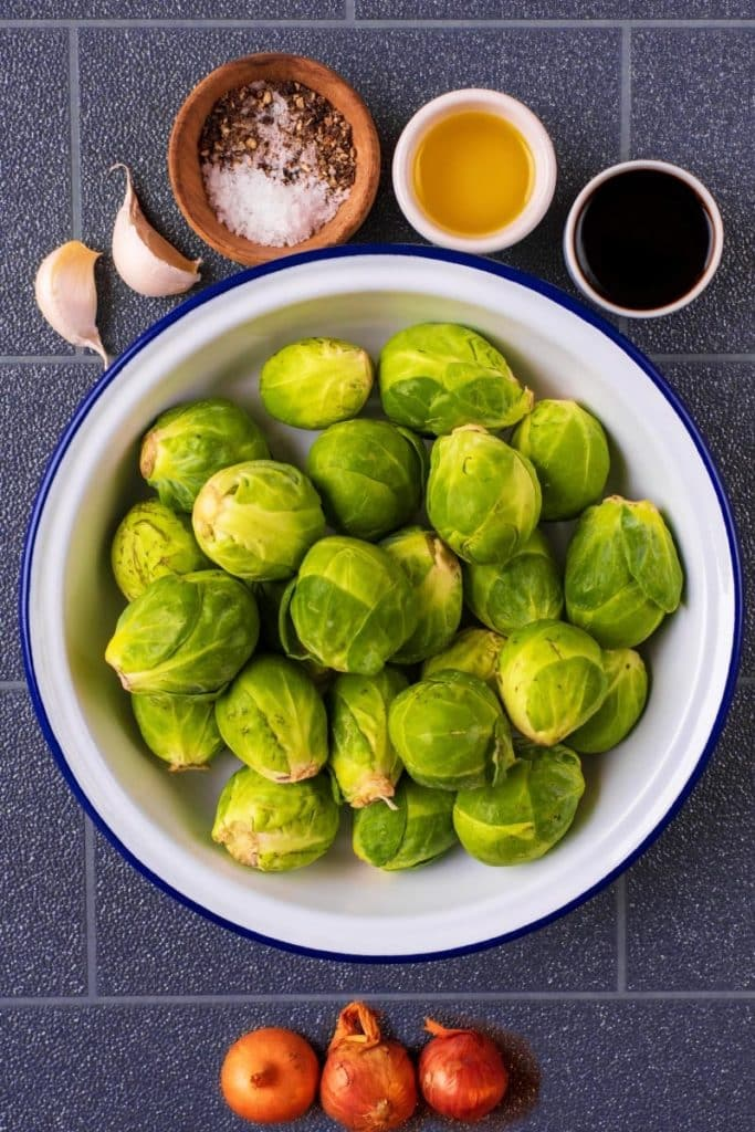 A bowl of uncooked brussels sprouts next to shallots, garlic cloves, oil and vinegar