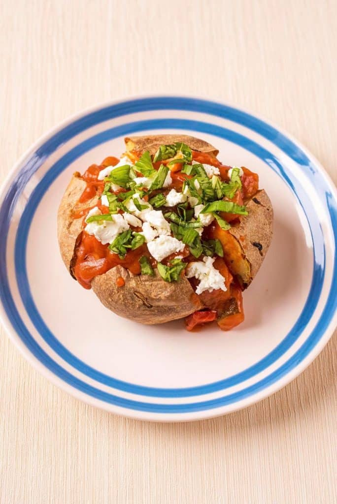 Baked Potato topped with Ratatouille and Goat's Cheese on a blue and white plate