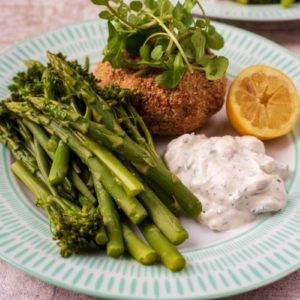 Tuna Fish cakes on a plate with vegetables, tzatziki and a lemon wedge