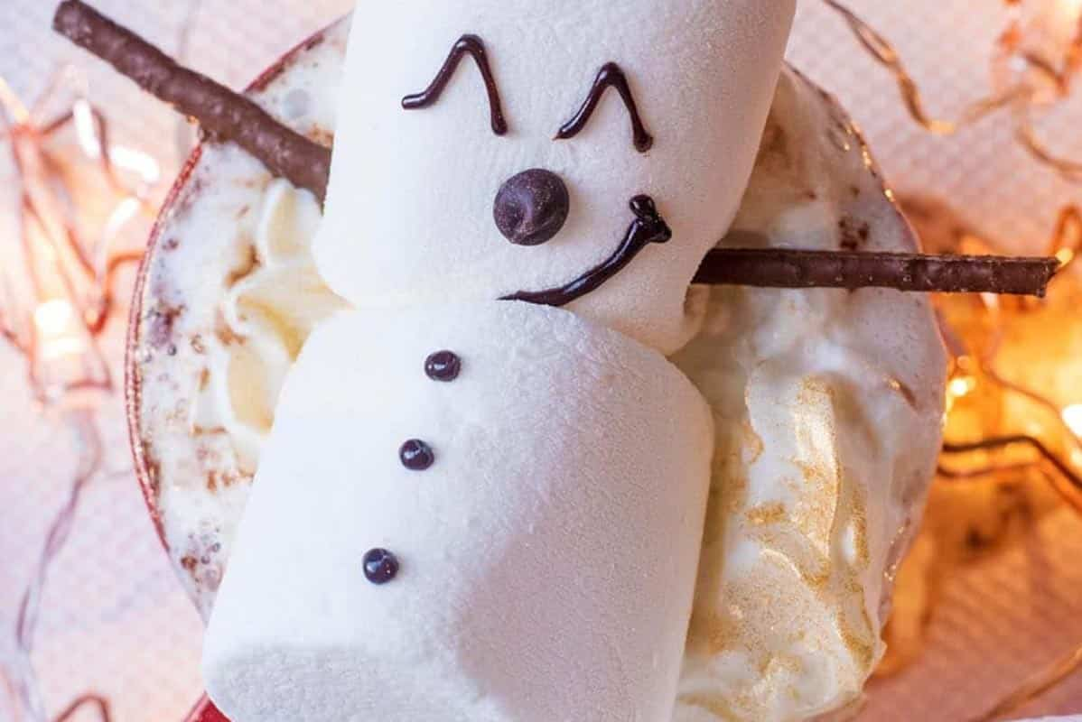 A marshmallow snowman on top of cream topped hot chocolate.