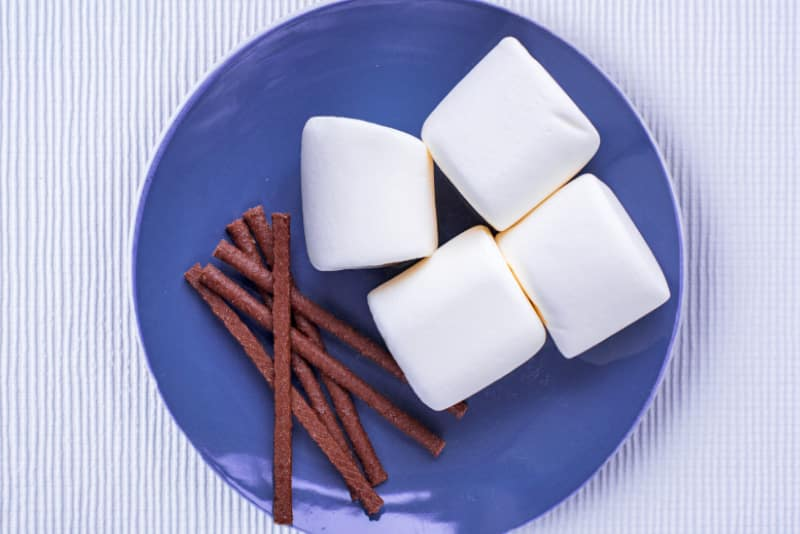 A blue plate with four giant marshmallows and some chocolate sticks