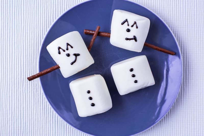Marshmallows on a plate with icing and chocolate sticks making them look like snowmen