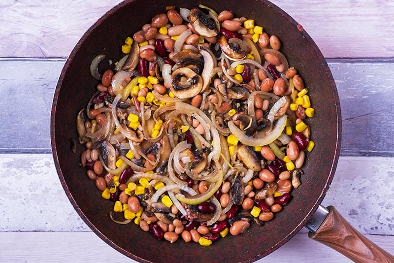 Mushrooms, onions, beans and sweetcorn frying in a pan