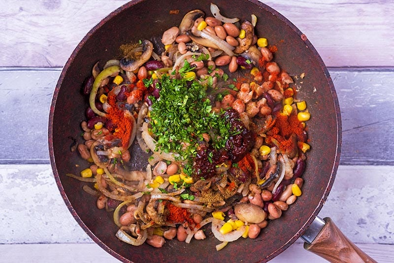 Mushrooms, onions, beans, sweetcorn, herbs and spices frying in a pan