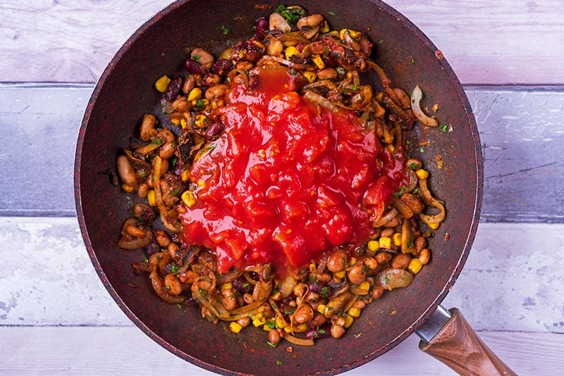 Bean burrito mix cooking in a frying pan