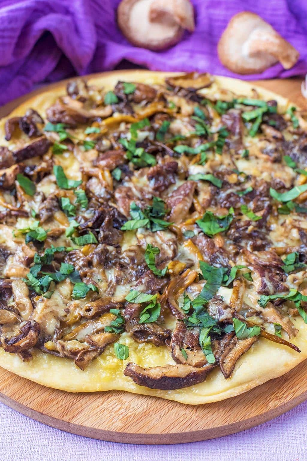 A mushroom pizza on a wooden serving board