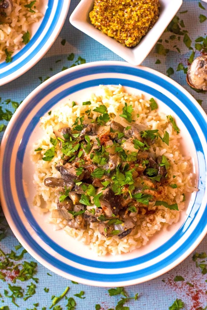 Vegetarian Stroganoff on top of rice with chopped parsley sprinkled on top
