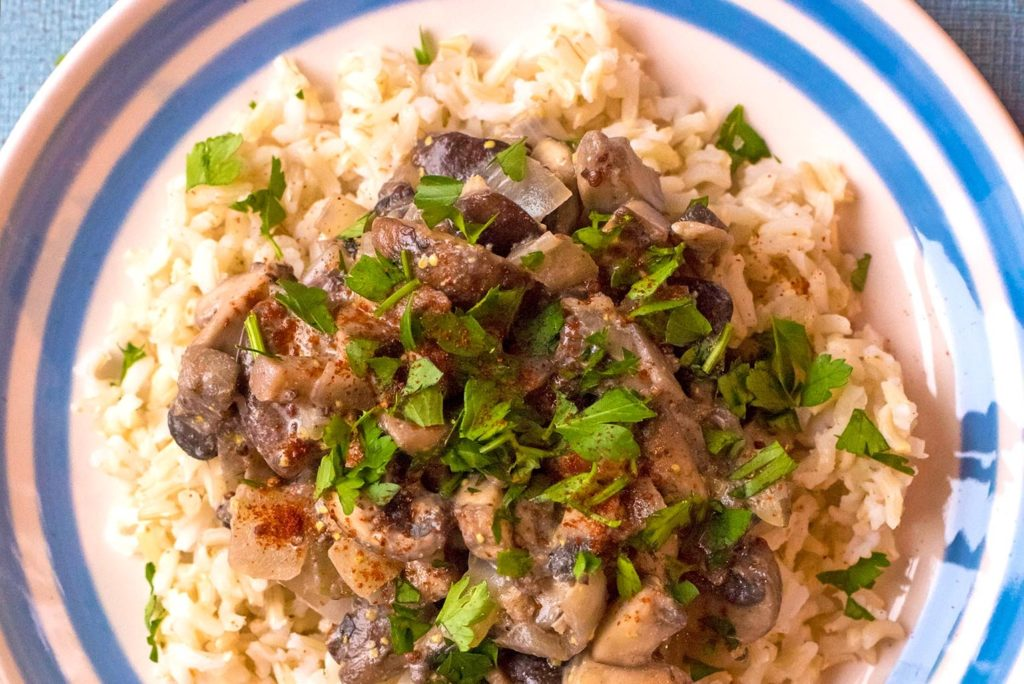 Mushroom Stroganoff on a blue and white plate with chopped parsley sprinkled on top