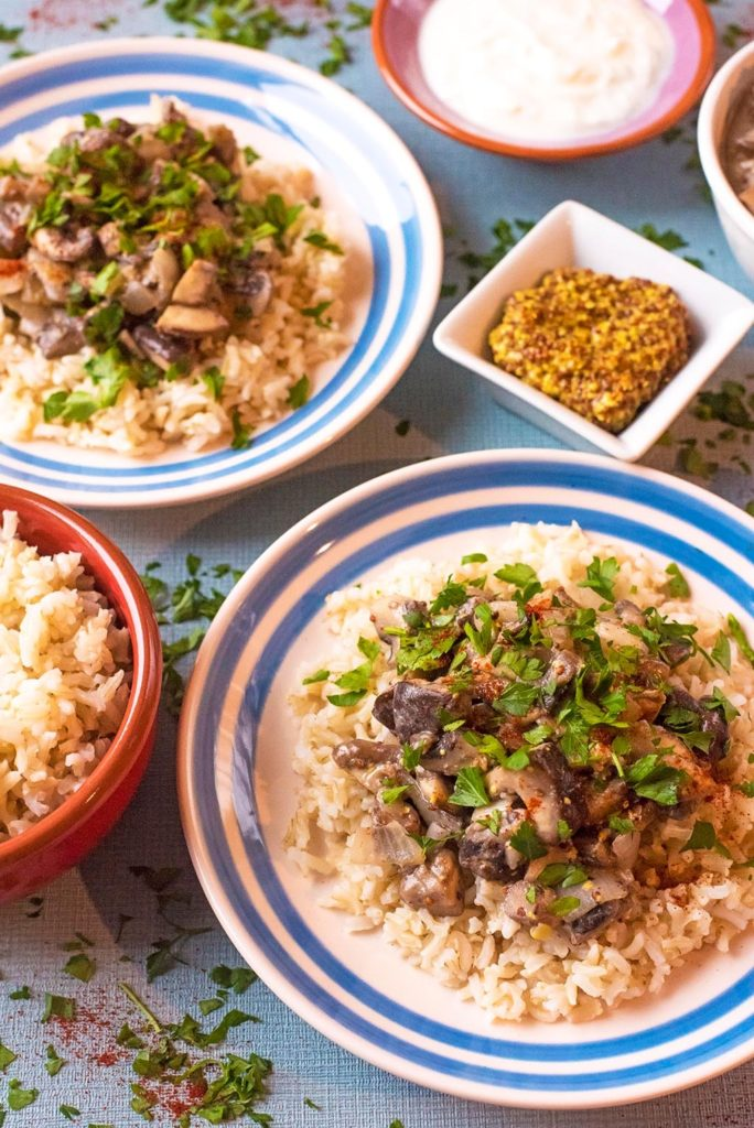 Mushroom Stroganoff served on two blue and white plates surrounded dishes of cream, mustard and rice