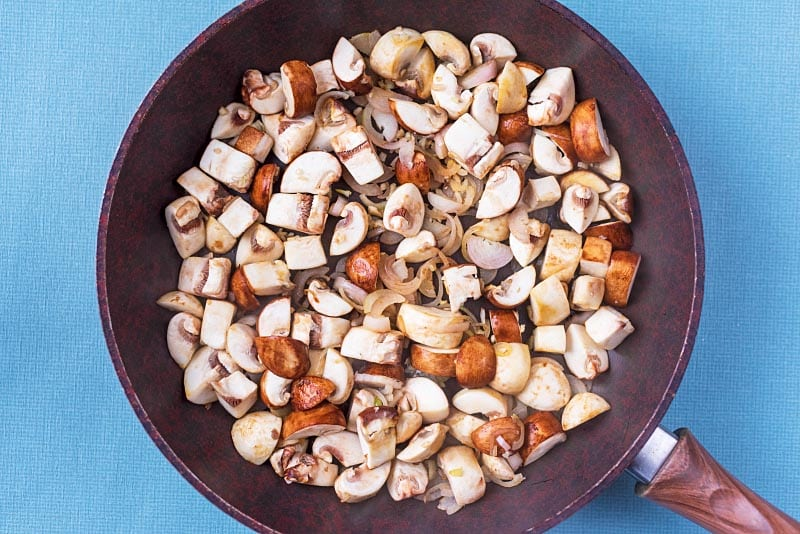 Chopped mushrooms and shallots in a frying pan