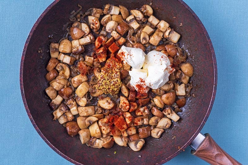 Cooked shopped mushrooms and shallots in a frying pan with dollops of cream and mustard. Paprika is sprinkled over everything