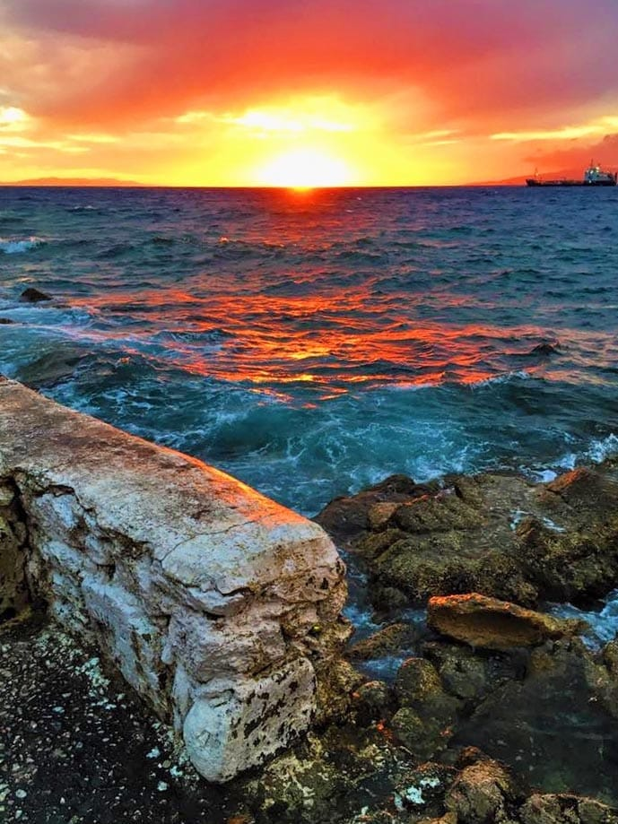 Sunset over a the sea with a wall in the foreground