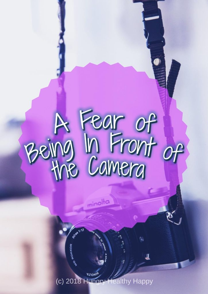 "A camera hanging by its strap with a text overlay saying ""A Fear of being in front of the camera"""