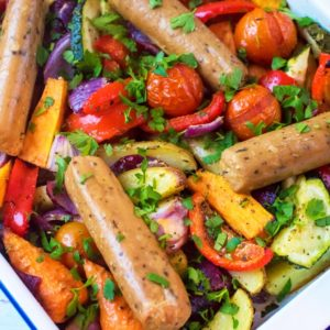 Honey and Mustard Sausage and Potato Traybake in a white enamel dish