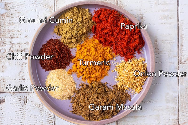 A plate with seven spices and their names labelled on them