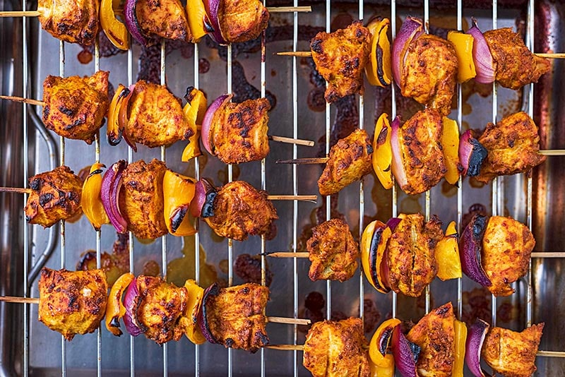 A cooking rack with eight cooked chicken tikka kebabs on it
