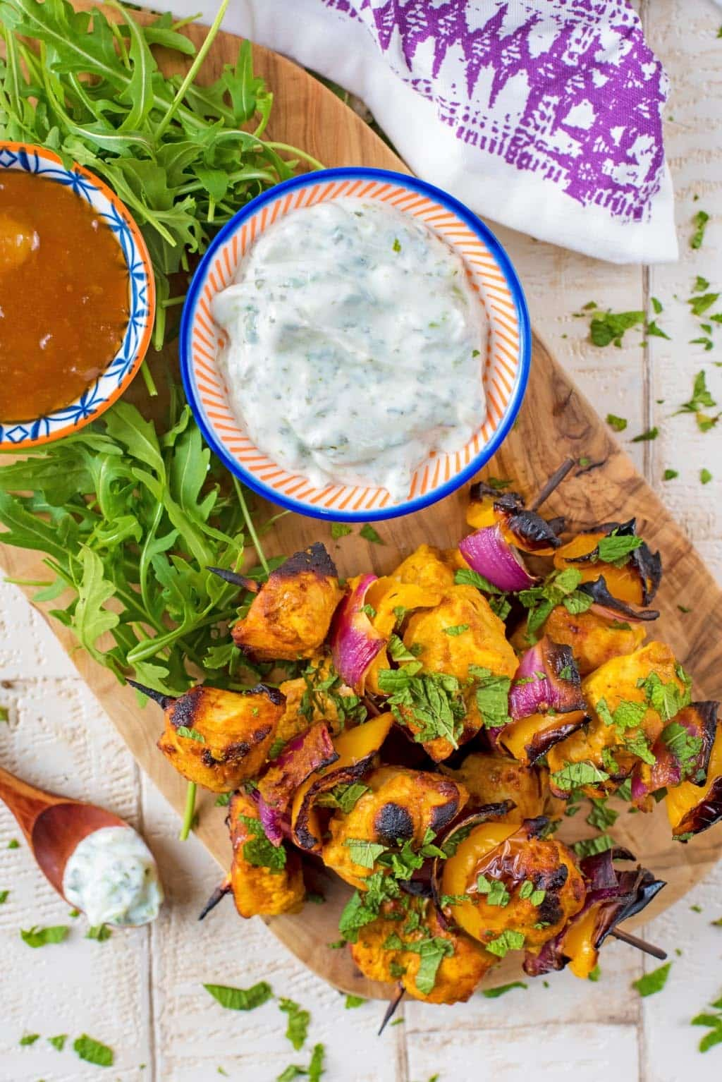Chicken Tikka Kebabs on a wooden serving board with a small dish of raita and a small dish of mango chutney