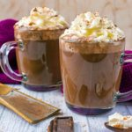 Cinnamon Mocha in two glass mugs topped with cream.