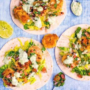 Three Crispy Prawn Tacos surrounded by lime wedges and spoons with salsa and sauce