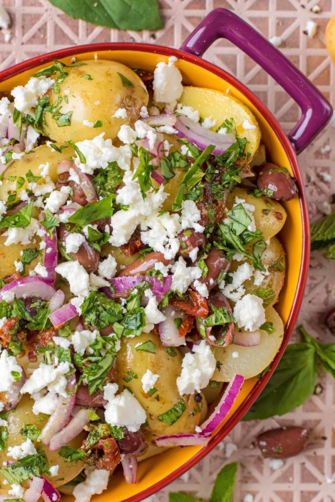 Mediterranean Potato Salad in an oval dish surrounded by basil leaves