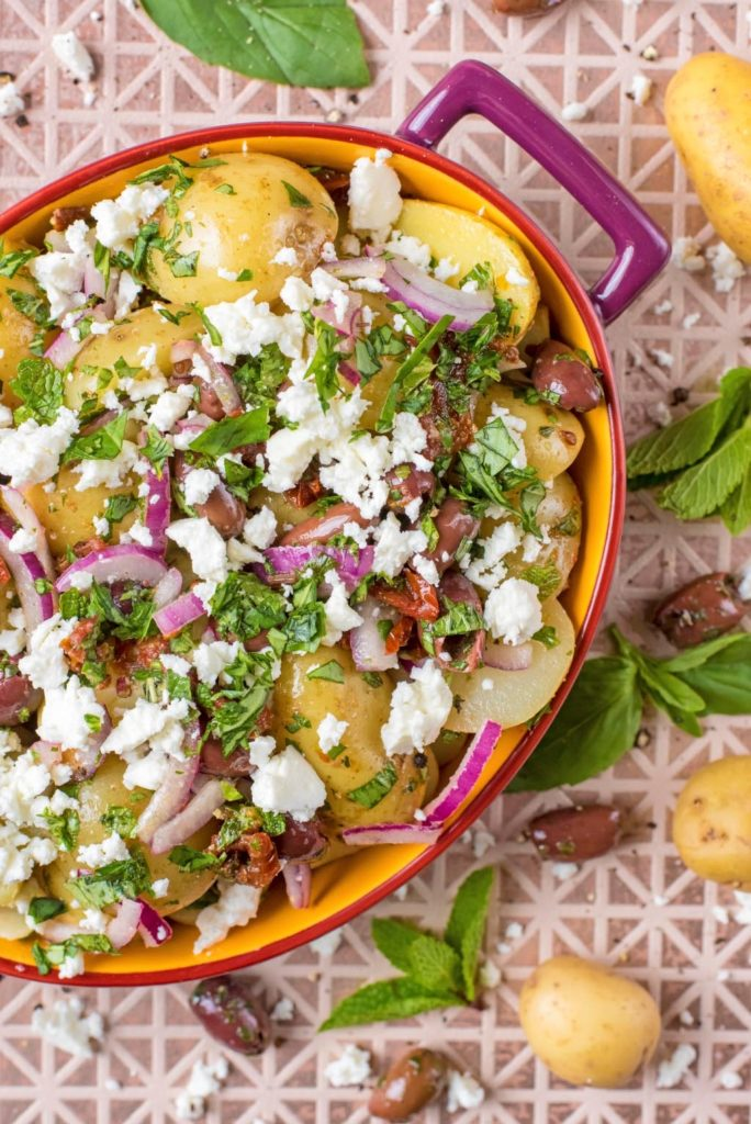 Potato Salad in an oval bowl topped with herbs and feta