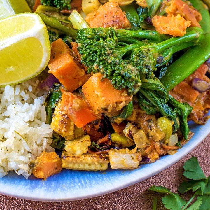 Vegetable Thai Green Curry on a blue plate with white rice and a lime wedge