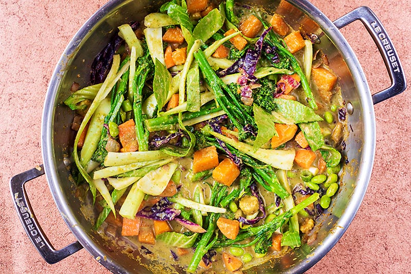 A large pan with vegetables cooking in a thai green sauce