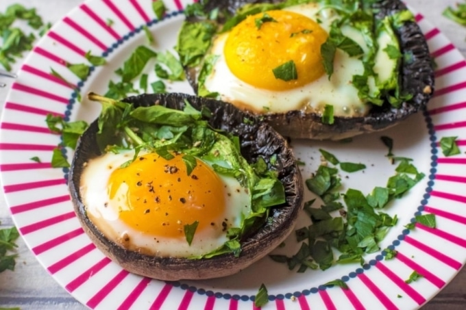 Eggs Baked in Portobello Mushrooms sat on a red and white plate