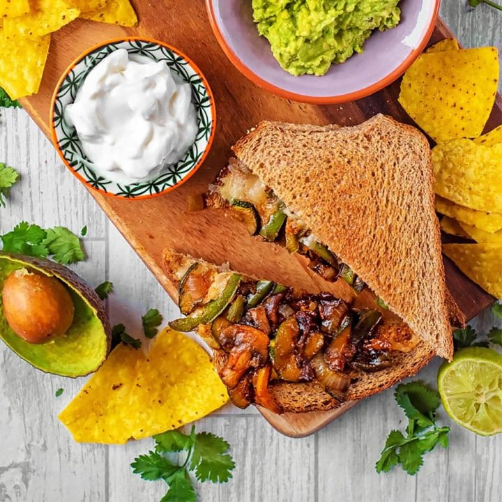 Fajita sandwich on a serving board with tortilla chips and guacamole