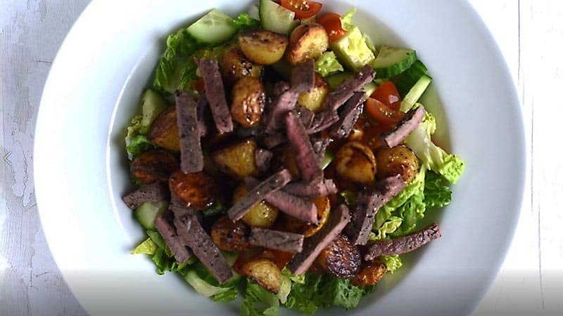 A large bowl containing lettuce, cucumber, tomato, potatoes and strips of steak
